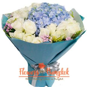 A large bouquet of gorgeous white roses and delicate hydrangeas.